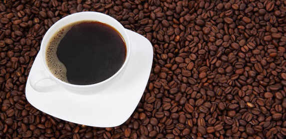 coffee beans with white cup filled with black coffee