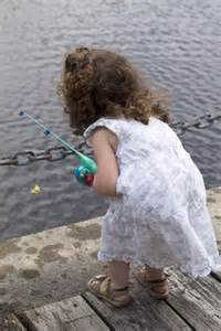 little girl in white dress fishing in pond