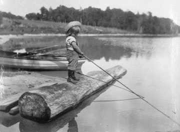 vintage black and white photo opf little girl fishing in lake with straw hat