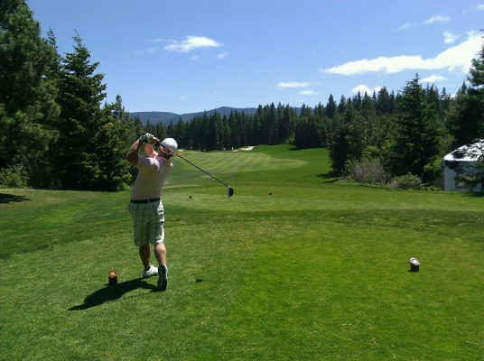 Senior golfer teeing off with driver